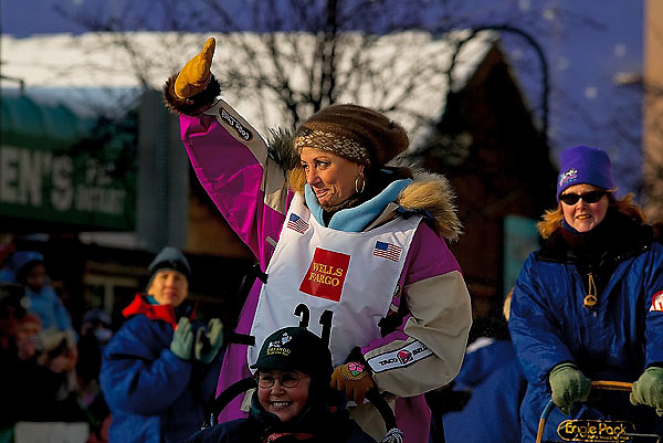 04 March 2006: Anchorage, Alaska - Fan favorite and cancer survivor, DeeDee Jonrowe of Willow, AK waves to the crowd cheering her on as she heads out during the Ceremonial Start in downtown Anchorage of the 2006 Iditarod Sled Dog Race.
