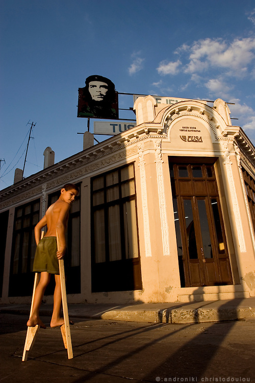Kid walking on stilts in Cienfuegos, in front of a building with a picture of Che Guevara on top of it. Cienfuegos - CUBA