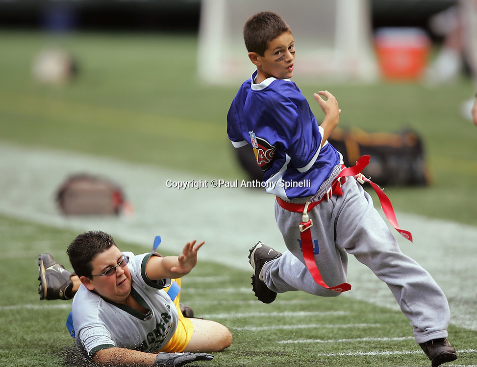 EAST RUTHERFORD, NJ - OCTOBER 1:  A young flag football player reaches in vain for another player running with the ball during an NFL Flag football exhibition at halftime of the New York Jets game against the Indianapolis Colts at the Meadowlands on October 1, 2006 in East Rutherford, New Jersey. The Colts defeated the Jets 31-28. ©Paul Anthony Spinelli