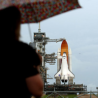 A member of the media stands in the rain as Shuttle Atlantis rests atop the launch pad at Kennedy Space Center Thursday, July 7, 2011, in Cape Canaveral, Fla. Shuttle Atlantis is scheduled to launch on Friday, July 8 and is the 135th and final space shuttle launch for NASA..  (AP Photo/Alex Menendez)
