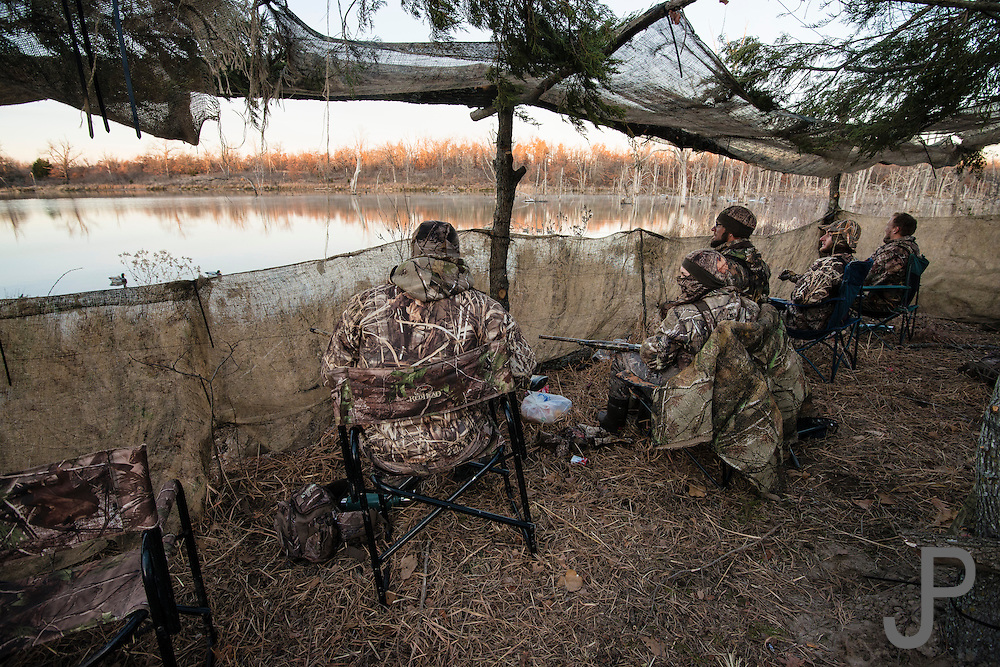 Hunters relax in a duck blind while hunting on a private watershed lake near Shamrock, Oklahoma