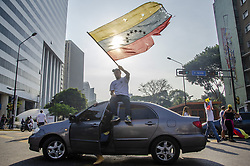April 30, 2019 - Caracas, Miranda, Venezuela - Protestors wave Venezuelan flags in the streets. Anti-government protesters and law enforcement officers clashed in Caracas after the opposition leader Juan Guaid— called for citizens to rise up against the president. (Credit Image: © Jimmy VillaltaZUMA Wire)