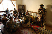 Members of the U.S. Army, Military Transition Team, and Iraqi army, 2nd Battalion, 2nd Brigade, 5th Division, have lunch with a local family during a four-day operation in New Baqubah, Iraq, on March 4, 2007. The purpose of the operation is to eliminate New Baqubah as an operating base for improvised explosive device building cells and key leaders of anti-Iraqi forces in Iraq.