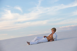 All American man in white clothes in White Sands, New Mexico sand dune