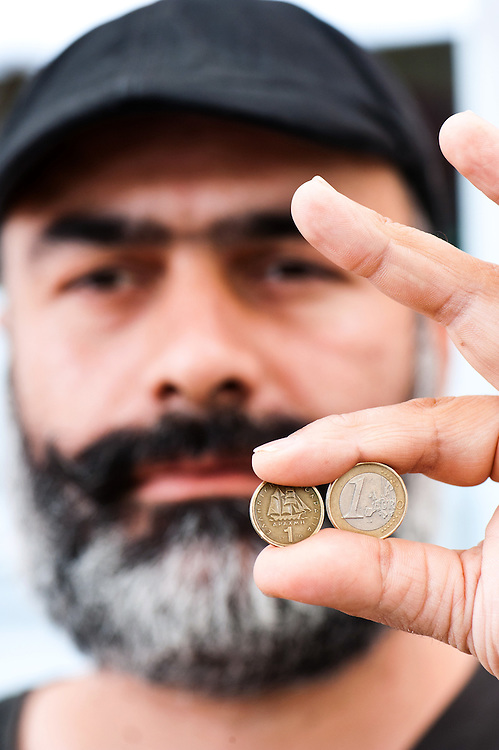 Cafe owner Nikos Bourbakis holding an old one drachma coin replaced by the euro in 2002 and a greek euro coin.