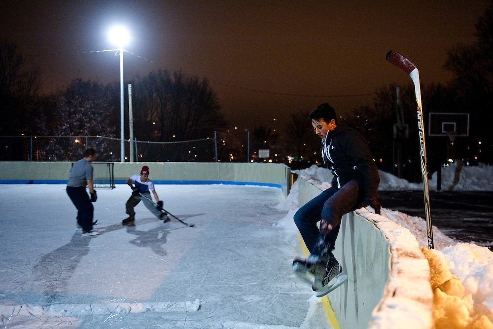 HOUGHTON, MI -DEC. 11, 2014: Jason Chynoweth, 16, climbs over the side of the hockey rink as Travis Bessner, 17, keeps the puck away from Gage Hawthorne, 17, behind him at a hockey rink on Edwards Street in Houghton, MI Thursday, Dec. 11, 2014. Lauren Justice for The New York Times