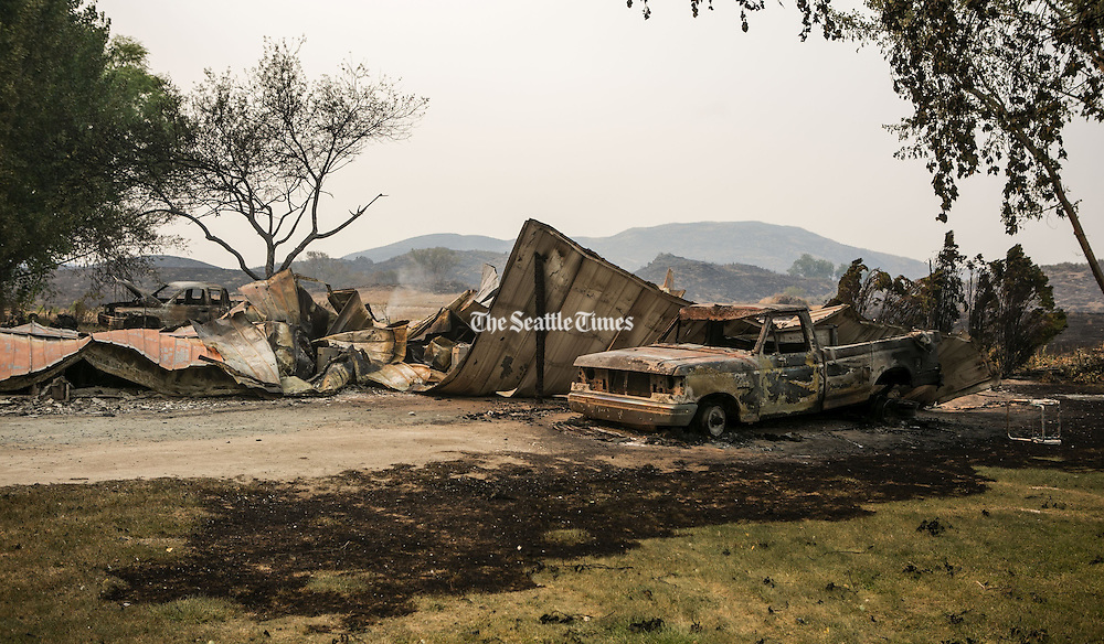 Burned-out trucks and a mobile home along Johnson Creek Road, north west of Omak as wildfires burn central Washington August 20, 2015.<br />