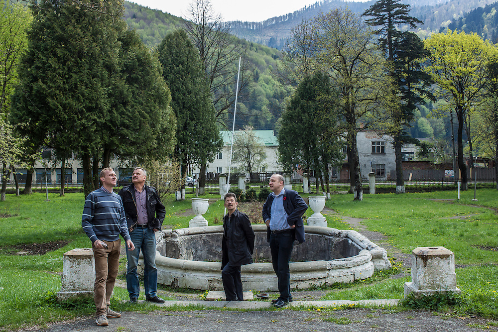 SKOLE, UKRAINE - MAY 1, 2015: Ostap Kozak, archivist for the organization Dolya, Volodymyr Kharchuk, deputy director of Dolya, Ihor Chudiovych, a local employee of the mayor's office, and Svyatoslav Sheremeta, Dolya's director, from left, outside a school which is believed to contain unmarked graves of Ukrainian partisans on its grounds in Skole, Ukraine. Dolya was formed to excavate and repatriate remains from World War II, though its focus is often on locating the graves of Ukrainian partisans killed by Soviet forces. CREDIT: Brendan Hoffman for The New York Times
