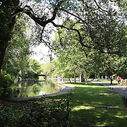People relax in Saint Stephen's Green, a city centre public park in Dublin, Ireland. The current landscape of the park was designed by William Sheppard, which officially opened to the public on Tuesday, July 27, 1880. The park is adjacent to one of Dublin's main shopping streets, Grafton Street. Dublin, Ireland. Photo Tim Clayton