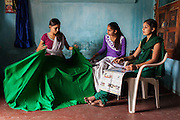 Video Volunteer videojournalist Niru J. Rathod (right), 24, looks at her two seamstress sisters Mukta, 22, and Kailash (center), 19, as she reads the newspaper at home in Surendranagar, Gujarat, India on 14 December 2012. While Niru's sisters have become seamstresses or housewives, Niru, the 8th child in a family of 11 girls born to a Dalit construction worker, has been using videography for social change since 2006. She shoots and produces her own short documentaries and is a committed video activist, having conducted hundreds of village video screenings where she also speaks to thousands of men, shattering their ideas about what a woman and a Dalit can do while bringing massive changes to the communities she documents. Photo by Suzanne Lee / Marie Claire France