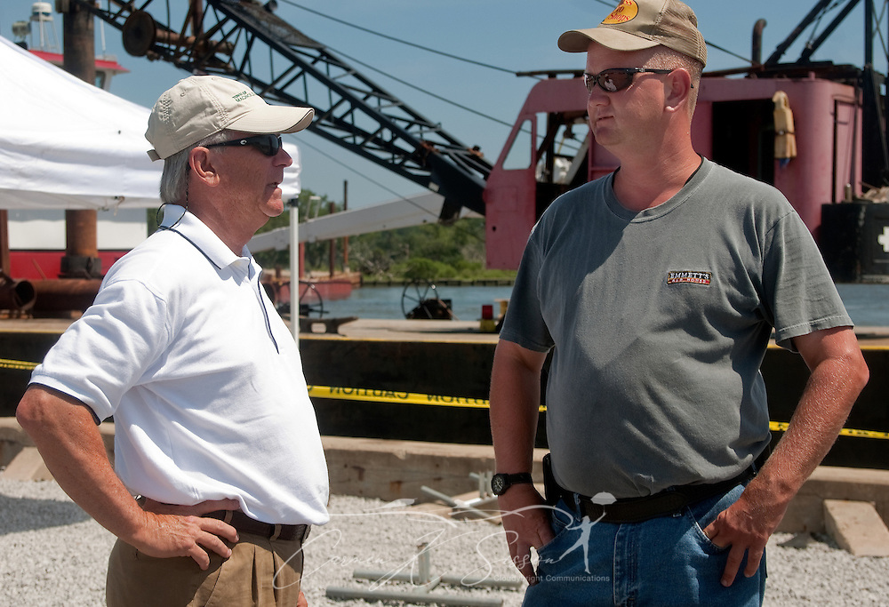 Magnolia Springs Mayor Charles Houser and Volunteer Fire Department Chief Jamie Hinton stand in front of a spud barge June 11, 2010 in Magnolia Springs, Ala. Houser and Hinton are leading the town in a fight to protect the area from encroaching oil by blocking the entrance to Weeks Bay with barges and layers of containment boom following the Deepwater Horizon oil rig explosion and BP oil spill. (Photo by Carmen K. Sisson/Cloudbright)