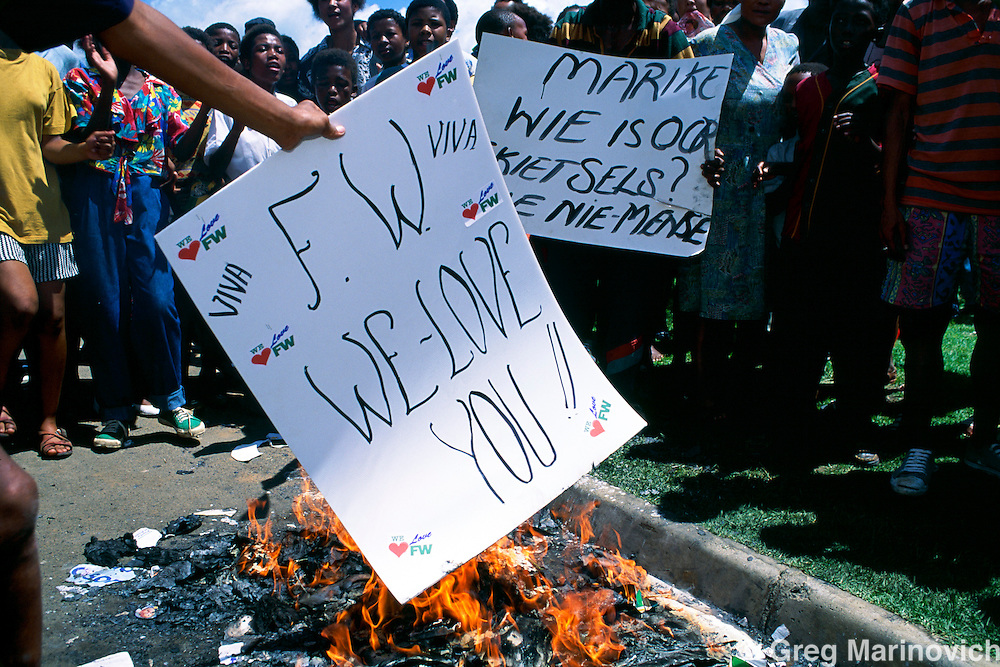 People burn posters welcoming Presidnt FW de Klerk at a rally in 1994 ahead of the first non racial elections in South Africa.