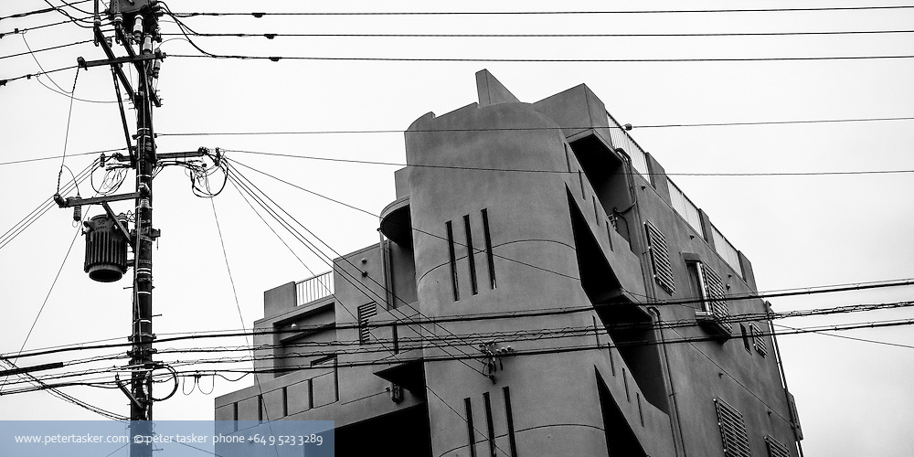 Array of power lines and power pole attachments, with interesting concreate building behind. Naha, Okinawa, Japan.