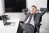 Businessman sleeping with sticky notes on eyes in office