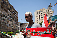 "A young man holds a poster that reads ""the people want"" with a photo of arrested president Morsi."