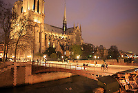 Tourists cross a bridge over a canal towards the Notre Dame Cathedral at night in Paris, France.