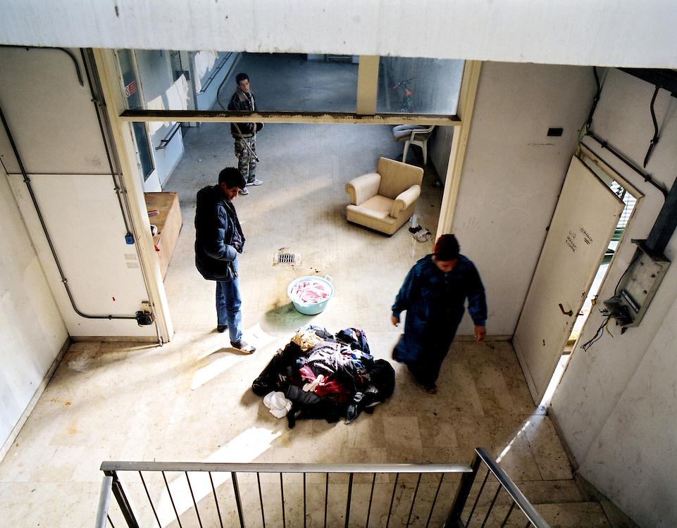 """ITALIEN / MIGRATION .Fluechtlinge, meist Illegale, leben in leer-.stehender Fabrik  unter z.T. sehr schlechten.Bedingungen..Die soziale Bewegung """"Movimento lotta per la.casa"""" setzt sich für die Rechte der Flüchtlinge.ein und besetzt Häuser um Wohnraum zu schaffen....HIER: in einem besetzten Haus. .Frau aus Marokko bei der Wäsche....Florenz, 08.11.2002"""