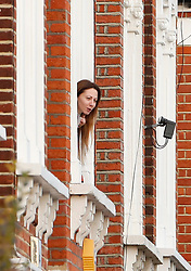 © Licensed to London News Pictures. 18/01/2019. London, UK. A woman looks out of the window of a neighbouring building at the scene  in Balham, south London where police are negotiating with a man who is inside the house with a knife. Photo credit: Peter Macdiarmid/LNP
