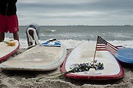 20110911 - Long Beach , NY - A surfer uses wax to attach an American flag to their surf board at a beach mass and ecumenical service at National Boulevard Beach in remembrance of 9/11 followed by a paddle out with surfers.  .Photo by Isabel Slepoy / LI Herald
