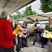 Nederland, Amsterdam , 21 mei 2012..Buurtbewoners Hans Paalman (midden) en Mieke van Kasbergen (rechts) van de Noordermarkt flyeren op de Noordermarkt uit protest tegen de plannen van de Gemeente om de aanlegsteiger bij de Noordermarkt toegankelijk te maken voor rondvaartboten waardoor dhr. Paalman met zijn woonboot zou moeten vertrekken en de hele buurt 1 grote toeristische attractie zou worden waardoor mogelijk de identiteit van de buurt verloren zou gaan..Hij is een beschaafd mens en dus is het hem niet aan te zien, maar woonbootbewoner Hans Paalman (64, consultant in ruste) is 'wit-verzengend-heet'. Stadsdeel Centrum wil bij de Noordermarkt 'een open afstapplaats' voor rondvaartboten maken, waardoor zijn boot moet verkassen. En die van zijn buurman ook. Paalman staat naast zijn 23 meter lange schip uit 1906, dat in de Prinsengracht ligt. Zijn blik verraadt diepgewortelde trots op het schip, dat hij onlangs geheel heeft laten opknappen.. Hans Paalman, Mieke van Kasbergen..Foto:Jean-Pierre Jans