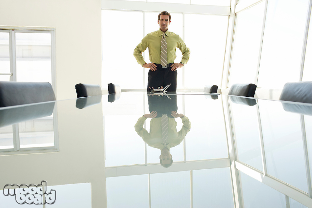 Businessman with hands on hips at conference table portrait