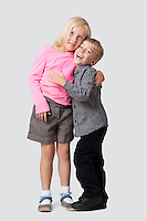 Portrait of cheerful young boy embracing sister over white background