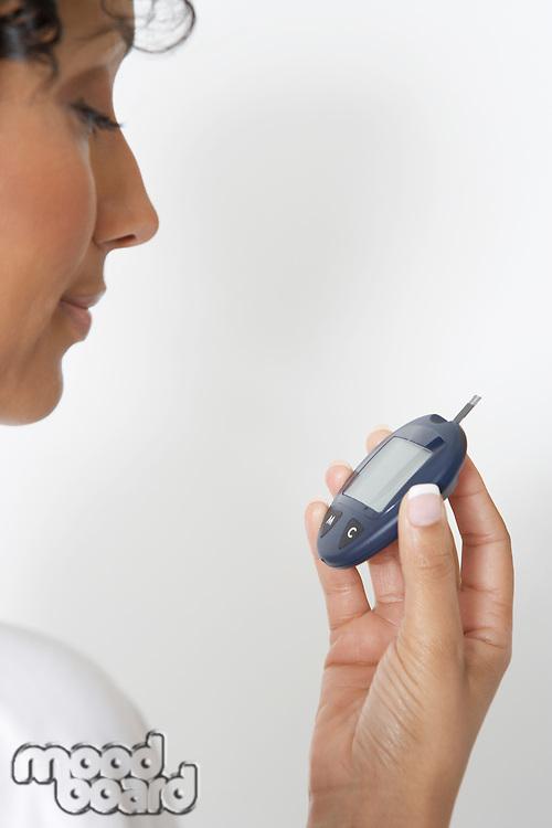 Woman checking diabetes test, close-up, studio shot