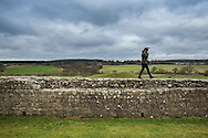 view of the Hadrian's wall near Brampton. a tourist walking on the ancient wall