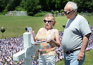 Bettylou Johnson, left, and Dave Horwatt of Levittown, Pennsylvania look at some memorial information during a ceremony for which the Delaware Valley Vietnam Veterans planted 65,000 flags at the Falls Township Community Park to honor the servicemen and servicewomen killed in Vietnam, Iraq and Afghanistan Sunday, June 12, 2016 in Fairless Hills, Pennsylvania.  The display is to mark Flag Day, which is June 14. (Photo by William Thomas Cain)