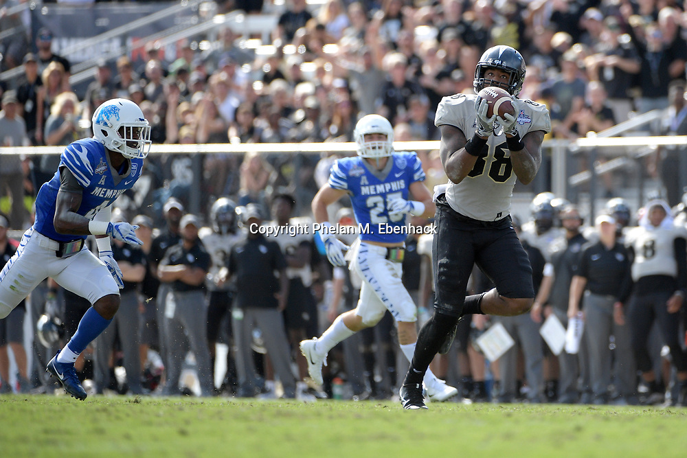 Central Florida tight end Jordan Akins (88) runs in for a touchdown after catching a pass in front of Memphis defensive back Austin Hall (25) and defensive back Josh Perry (4) during the first half of the American Athletic Conference championship NCAA college football game Saturday, Dec. 2, 2017, in Orlando, Fla. (Photo by Phelan M. Ebenhack)