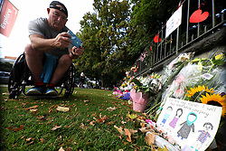 March 18, 2019 - Christchurch, New Zealand - A disabled person take pictures of flowers and messages of condolence at a memorial outside the Botanical Gardens, as a tribute to victims of the mosque attacks in Christchurch on March 17, 2019. At least 50 people were killed and 36 injured in mass shootings at two mosques in the New Zealand city of Christchurch Friday, 15 March. A 28-year-old Australian born man appeared in Christchurch District Court on Saturday charged with murder. (Credit Image: © Sanka Vidanagama/NurPhoto via ZUMA Press)