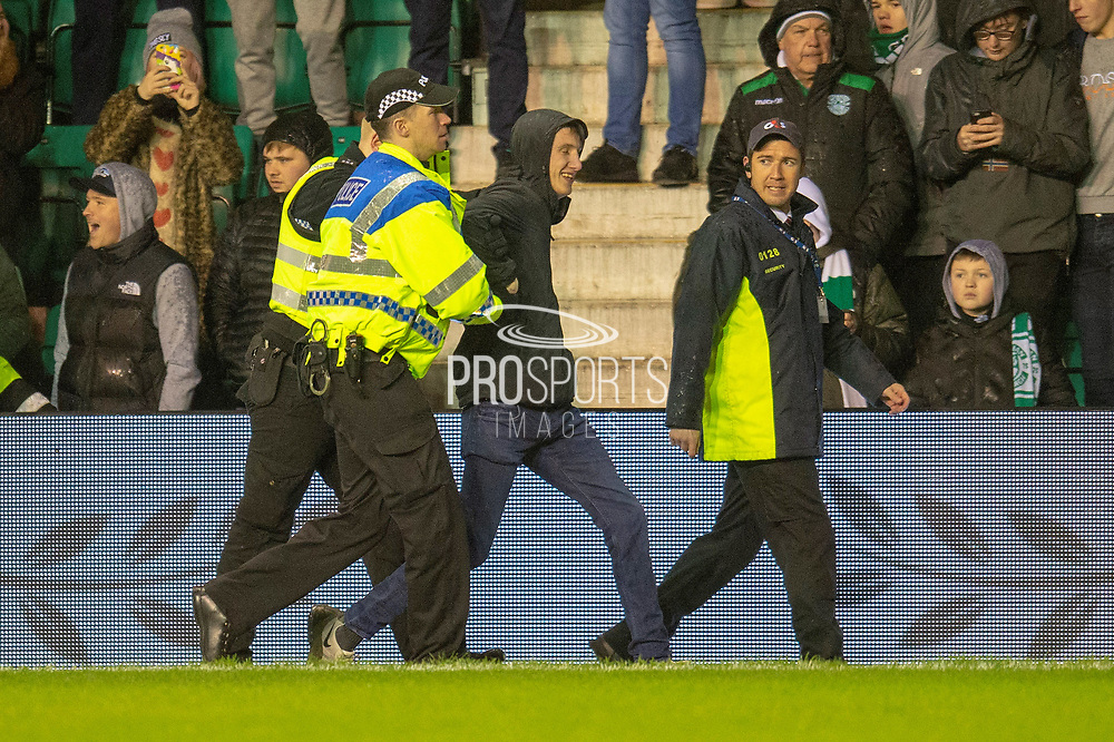 A fan is led away by the Police after he ran onto the pitch during the Ladbrokes Scottish Premiership match between Hibernian and Rangers at Easter Road, Edinburgh, Scotland on 8 March 2019.