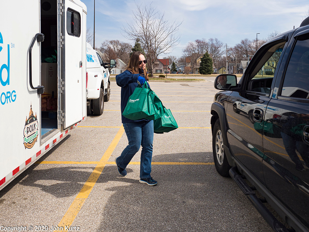 """17 MARCH 2020 - DES MOINES, IOWA: CARRIE LARUE, of the Des Moines Area Religious Council (DMARC) takes bags of food to a family waiting in their car in the parking lot of Carver Elementary School in Des Moines. Des Moines Public Schools are closed for at least 30 days because of the Coronavirus outbreak. Des Moines area religious organizations and food banks are working together to bring free food to children in at risk communities. Volunteers and workers are practicing """"social distancing"""" by leaving the food packages on the pavement and recipients pick up the packages. Tuesday, the Governor of Iowa ordered all restaurants and bars to close or go to take out only. The Iowa Department of Public Health has urged all public buildings, like libraries and schools, to close, and all schools in Iowa are closed for at least 30 days.    PHOTO BY JACK KURTZ"""