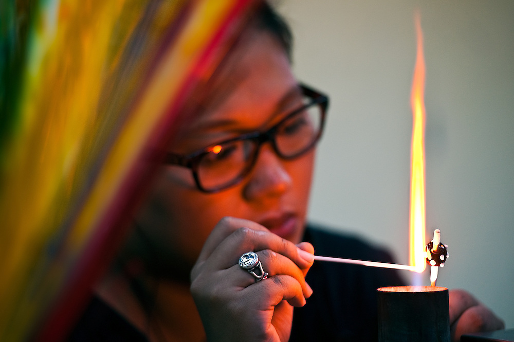 Colorful glass rods frame a glass bead artisan at Dragonfly Bead Art Studio, Sandimen, Pingtung County, Taiwan