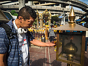 21 AUGUST 2015 - BANGKOK, THAILAND: A man lights incense before praying at Erawan Shrine Friday. The Bangkok Metropolitan Administration (BMA) held a religious ceremony Friday for the Ratchaprasong bomb victims. The ceremony started with a Brahmin blessing at Erawan Shrine, which was the target of a bombing Monday night. After the blessing people went across the street to the plaza in front of Central World mall for an interfaith religious service. Theravada Buddhists, Mahayana Buddhists, Muslims, Sikhs, Hindus, and Christians participated in the service. Life at the shrine, one of the busiest in Bangkok, is returning to normal. Friday the dancers and musicians who perform at the shrine resumed their schedules.       PHOTO BY JACK KURTZ