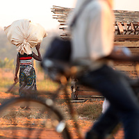 A woman balances a large bag of goods on her head as a man rides by on a bicycle at an informal market in Chimoio of Mozambique, Africa.