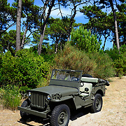 """Unmanned WW2 or WWII Jeep Willis in excellent condition parked on sand. This vehicle has lived a 'revival' and recently has come very much """"en vogue"""" as a 'casual summer caddy' among wealthy people in this part of France."""