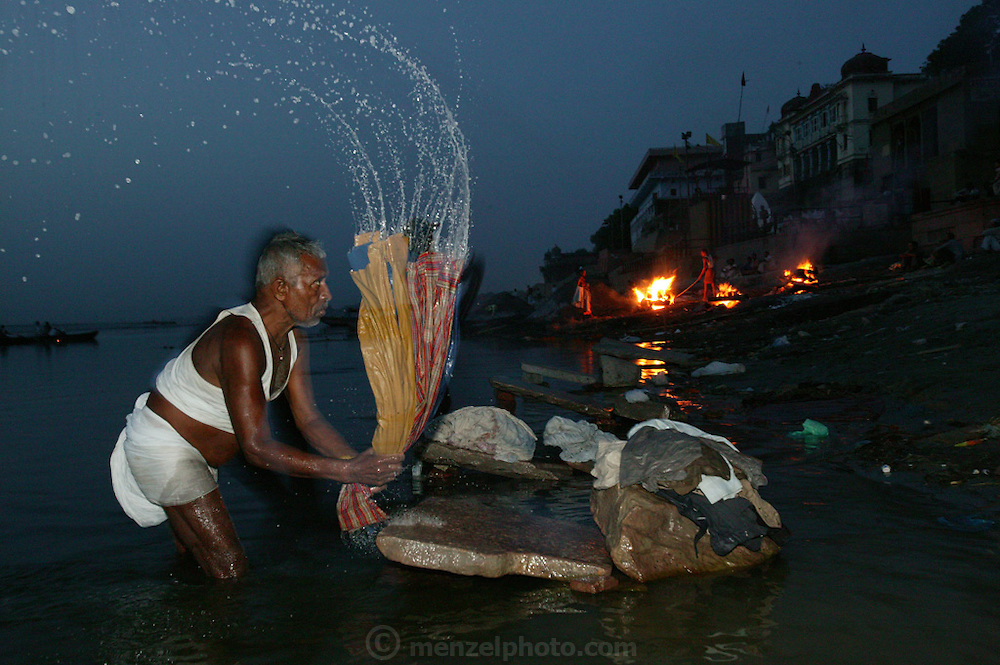 Death is part of the fabric of life for Hindus and like much of Indian society, takes place in open view. In the early morning men and women wash clothes in the river, slapping dhoti, saris, and other pieces of clothing against rocks and cement slabs as others tend to the bodies burning on the shore at Harishchandra Ghat. A man uses a long bamboo pole that once was part of the litter fashioned to carry a body to the cremation grounds at Harishchandra Ghat to flip the unburned legs and arms back into the fire. He uses the pole to smash the skulls open as well so that it burns more easily. The Harishchandra Ghat (also known as the Harish Chandra Ghat) is the smaller and more ancient of the two primary cremation grounds in Varanasi, on the banks of the Ganges River.