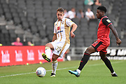 Milton Keynes Dons defender Callum Brittain (25) passes under pressure from Grimsby Town striker JJ Hooper (9) during the EFL Sky Bet League 2 match between Milton Keynes Dons and Grimsby Town FC at stadium:mk, Milton Keynes, England on 21 August 2018.