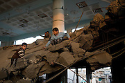 Palestinian children scavenge what they can find from inside the bombed out interior of Al Abrar mosque in downtown Rafah, Gaza January 15, 2009. Al Abrar, the largest mosque in Rafah was targeted by the Israeli Air Force in the early hours of Thursday morning presumably for alleged weapons or explosive caches stored at the site, a claim local Palestinians dispute. Photo by Scott Nelson/World Picture Network for the New York Times.