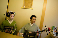 Miehina, a 20 year old maiko ( an apprentice geisha) from the Miyagawacho district of Kyoto, prepares to sing for her evening clients, accompanied on the 'shamisen' musical instrument be the Mama-san (owner and boss) of the house, in the tea house where she lives and works, Kyoto, Japan, Sunday, May 18th 2008.