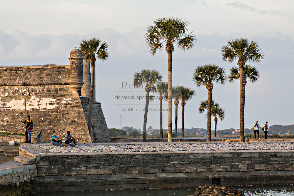 People look out at Matanzas Bay from the walls of the Castillo de San Marcos in St. Augustine, Florida. St Augustine is the oldest city in America.