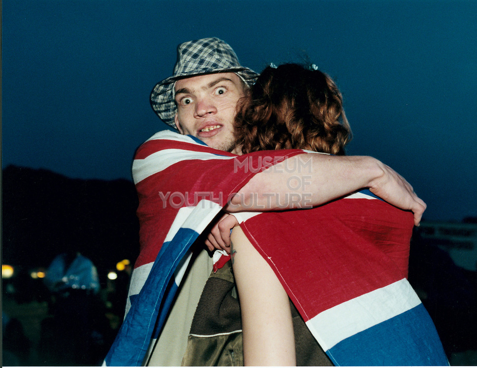 Young man and woman hugging under a union jack blanket.