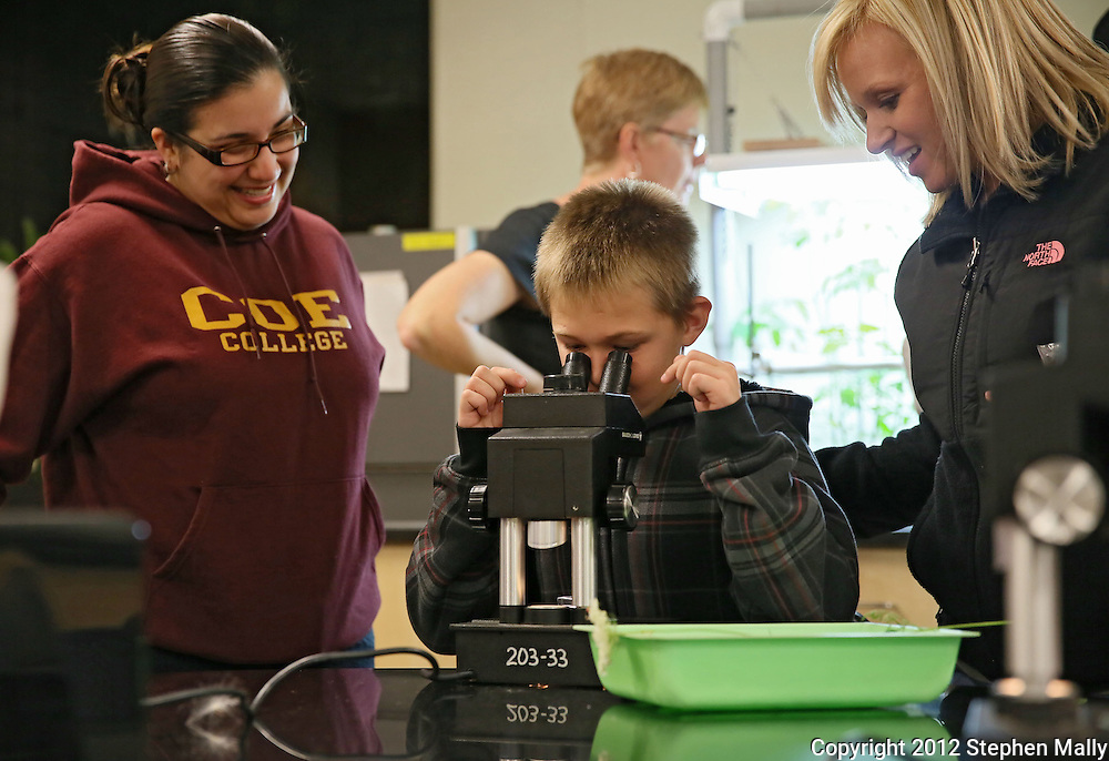 Coe College freshman Veronica Saucedo-Biagas (from left), of North Liberty, helps Keaton Frye, 9, of Cedar Rapids, look at a small spider under a microscope as his mother, Samantha Frye looks on during the 10th annual Playground of Science at Peterson Hall on the Coe College campus in Cedar Rapids on Thursday, October 25, 2012.