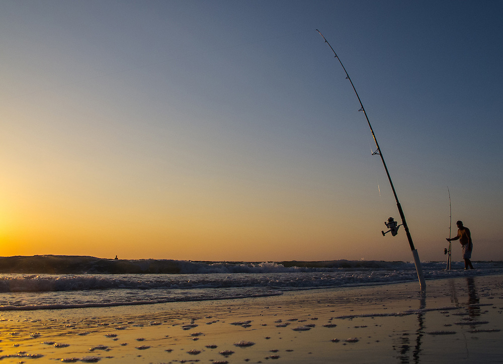 Fishing along the shoreline during sunset at the beach.