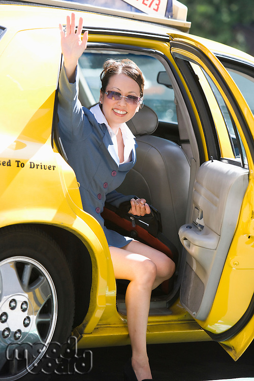 Young businesswoman disembarking from taxi