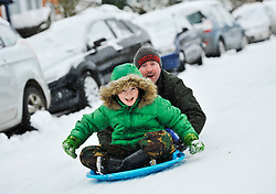 © Licensed to London News Pictures. 20 January 2013. Chipping Norton, Oxfordshire. Patrick and his son Ryan Hurley. Probably the best Street in England for sledging? Residents of The Leys in Chipping Norton have made a super sledging run in the road. The local children even prevented council workers from salting the road by sitting down across the road to block the gritters. Everyone who live in the Leys seems to love the sledging run and have even joked that they want to apply for a ski lift to be installed for future years fun.. Photo credit : MarkHemsworth/LNP