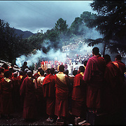 Surrounded by crimson robed Tibetan monks, the Dalai Lama performs a puja in Dharamsala,India.©1986