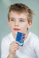 Close-up of little boy holding credit card over gray background
