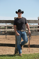 cowboy in a black tee shirt leaning against a fence on a ranch